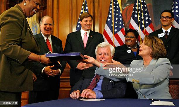 Speaker of the House Nancy Pelosi hands the College Cost Reduction Act of 2007 to Clerk of the House Lorraine C Miller after signing the bill at the...
