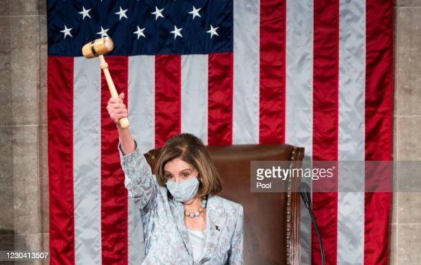 Speaker of the House Nancy Pelosi holds the Speakers gavel in the air on the House floor in the Capitol after becoming Speaker of the 117th Congress...