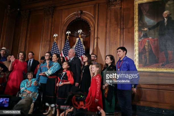 Speaker of the House Nancy Pelosi poses for photographs with Rep Deb Haaland and her family in the Rayburn Room at the US Capitol January 03 2019 in...