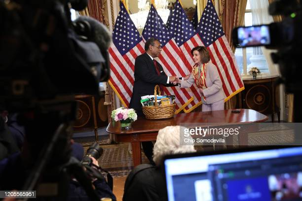 Speaker of the House Nancy Pelosi presents Rep Emanuel Cleaver with a basket with items from the San Francisco area including Ghirardelli chocolate...