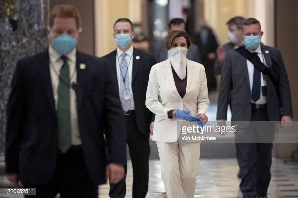 Speaker of the House Nancy Pelosi removes a pair of rubber gloves while returning to her office after the start of a vote on the latest stimulus...