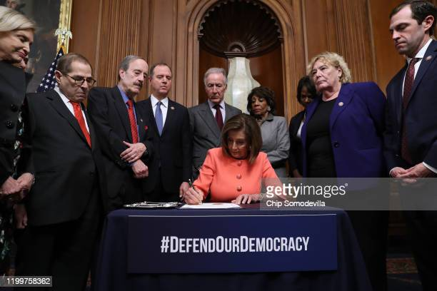 S Speaker of the House Nancy Pelosi signs the articles of impeachment against President Donald Trump during an engrossment ceremony with Rep Carolyn...