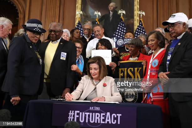 Speaker of the House Nancy Pelosi signs the Fostering Undergraduate Talent by Unlocking Resources for Education Act during the enrollment ceremony in...