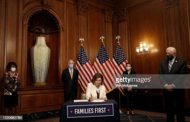 Speaker of the House Nancy Pelosi signs the latest stimulus package, the Paycheck Protection Program and Healthcare Enhancement Act, at the U.S....