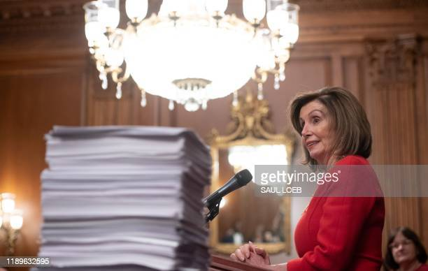 US Speaker of the House Nancy Pelosi speaks alongside a stack of legislation the House has passed as she holds a press conference with fellow...