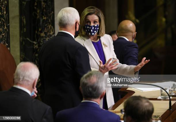 Speaker of the House Nancy Pelosi talks with Vice President Mike Pence talk after the conclusion of the count of electoral votes in the House Chamber...