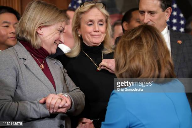Speaker of the House Nancy Pelosi touches a ring that belonged to former Rep. John Dingell that his wife Rep. Debbie Dingell wears around her neck...