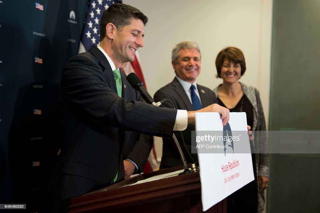 US Speaker of the House of Representatives Paul Ryan adjusts his placard after it was bumped as he spoke during a press conference after the Republican Conference meeting on Capitol Hill in Washington, DC, on September 13, 2017. /