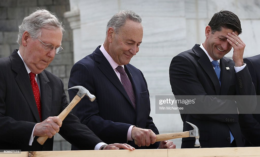 Speaker of the House Paul Ryan (R) (R-WI) laughs as Sen. Chuck Schumer (C) (D-NY) and Senate Majority Leader Mitch McConnell drive nails into a piece of lumber at the 'First Nail Ceremony' September 21, 2016 outside the U.S. Capitol in Washington, DC. The ceremony marked the official launch of construction on the Inaugural platform where the next President of the United States will take the oath of office on Friday, January 20, 2017.