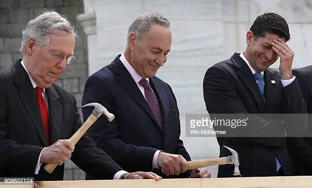 Speaker of the House Paul Ryan laughs as Sen Chuck Schumer and Senate Majority Leader Mitch McConnell drive nails into a piece of lumber at the...