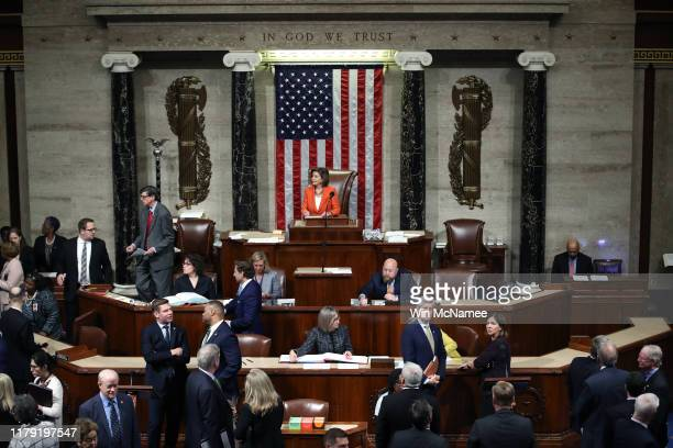 Speaker of the House US Rep Nancy Pelosi presides over the US House of Representatives as it votes on a resolution formalizing the impeachment...