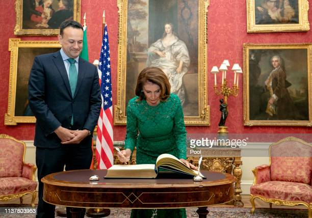Speaker of the U.S. House of Representatives Nancy Pelosi signs the visitor's book next to Taoiseach Leo Varadkar in the State Apartments in Dublin...