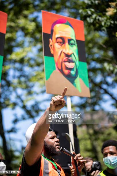 A speaker wearing a construction hat holds up a number 1 finger with a painted portrait of George Floyd with the PanAfrican colors of Red Black and...