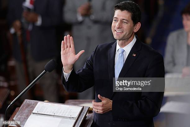 Speakerelect of the House Paul Ryan waves to his supportes guests and members of his family in the House chamber at the US Capitol October 29 2015 in...