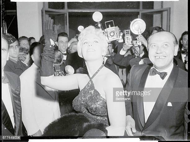 Speaking of beauty Hollywood's Kim Novak shows plenty for photographers clustered around her She's just finished work in The Eddy Duchin Story