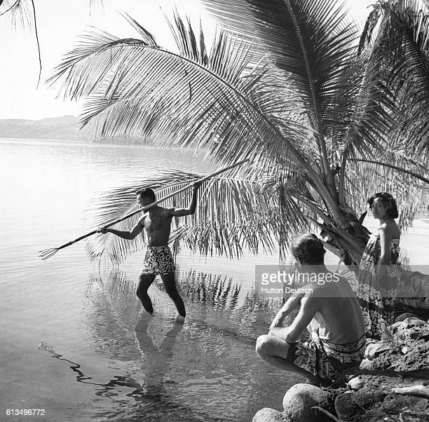 A spear fisherman studies the waters of a lagoon in Tahiti getting ready to catch some fish