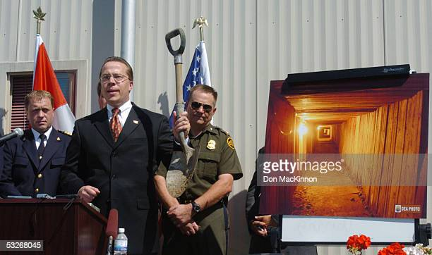 Special Agent in charge of DEA Rod Benson holds up a shovel that was used to dig the tunnel under the border while inspector Pat Fogarty and Ron...