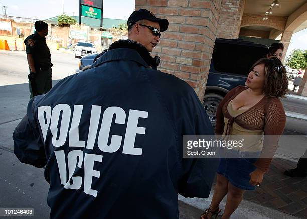 Special agents from Immigration and Customs Enforcement and Border Patrol question a woman while her vehicle is searched after she was stopped...