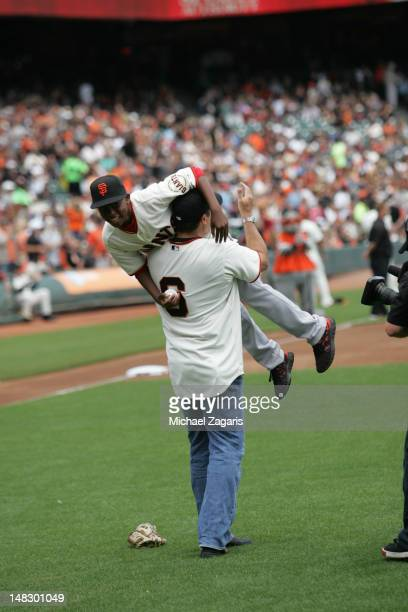 Special Assistant JT Snow of the San Francisco Giants carries Darren Baker reenacting Snow saving Baer during the 2002 World Series on the field...