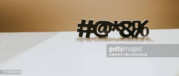 special characters casting a shadow on a white surface, with space for copy. - symbolism stock pictures, royalty-free photos & images