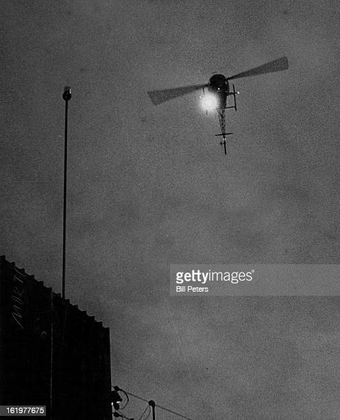 Special Crime Aerial Reconnaissance helicopter hovers over an installed strobe alarm as a crew member determines the address of a crime by receiving...