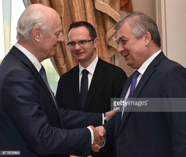 UN Special Envoy for Syria Staffan de Mistura shakes hands with Russian mediator Alexander Lavrentiev as they attend the fourth round of Syria peace...