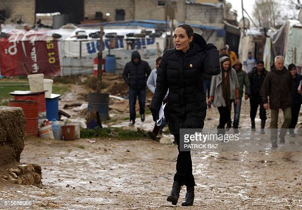 Special envoy of the UN High Commissioner for Refugees US actress Angelina Jolie walks under the rain as she arrives for a press conference at a...