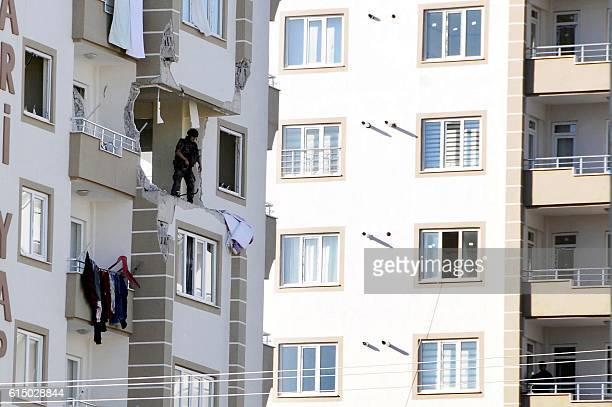 TOPSHOT A special force police officer inspects a damaged apartment at the explosion site on October 16 2016 near the Syrian border in Gaziantep...