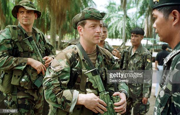 S Special Forces Captain Todd Thompson from California speaks with Col Reynato Padua of the Philippine Scout Rangers as Master Sgt Lonnie Baker of...