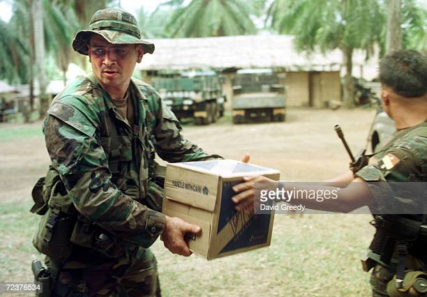 S Special Forces Master Sgt Lonnie Baker of Montana helps unload gear February 20 2002 at the Scout Rangers camp in Isabela on the southern...