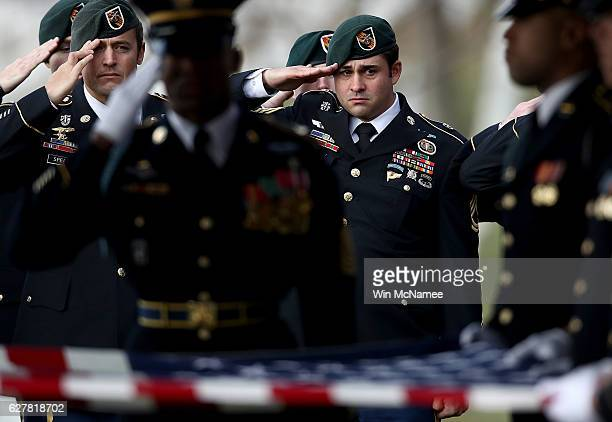 """Special forces members salute during the playing of """"Taps"""" during the burial service for U.S. Army Staff Sgt. Kevin J. McEnroe at Arlington National..."""