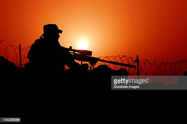 A U.S. Special Forces soldier armed with a Mk-12 Sniper Rifle at sunset.