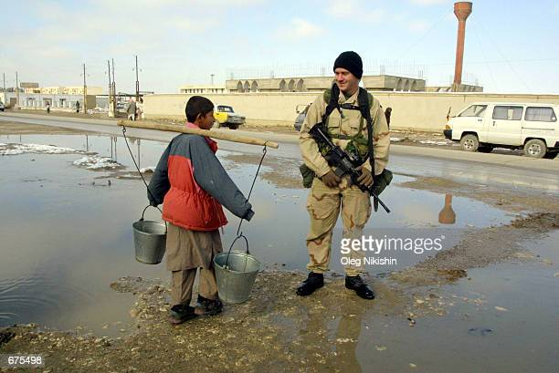 S special forces soldier talks to a young Afghan boy as he walks along the streets of MazareSharif December 4 2001 in Afghanistan About two dozen US...