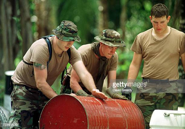 S Special Forces Specialist Billie Poulton of Bonners Ferry Idaho and Staff Sgt Tim McGuire of Trevor City Michigan push a barrel into a truck while...