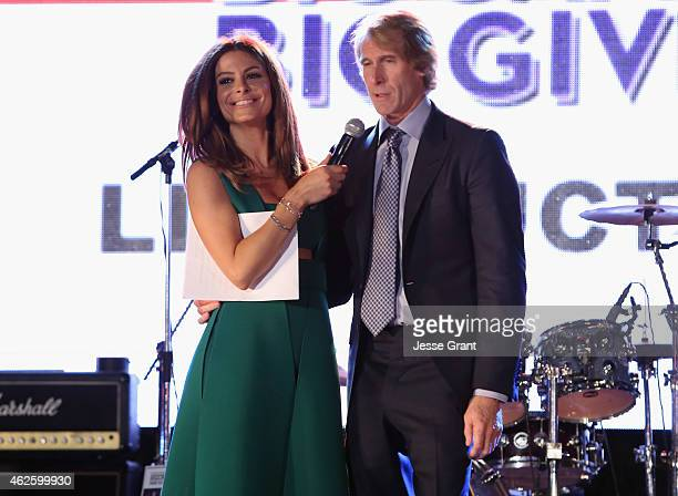 Special guest Maria Menounos and film producer/director Michael Bay speak onstage at The Giving Back Fund's Big Game Big Give at the home of Erika...