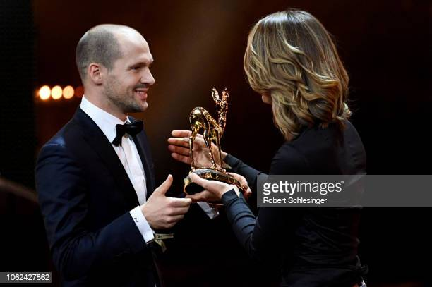 'Special Jury' winner Patrick Lange receives his award from Jessy Wellmer on stage during the 70th Bambi Awards show at Stage Theater on November 16...
