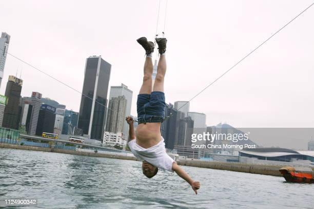 Special lunch time performance by Beijing artist Li Wei who dangles himself on a crane at the waterfront by Royal Hong Kong Yacht Club Kellett Island...