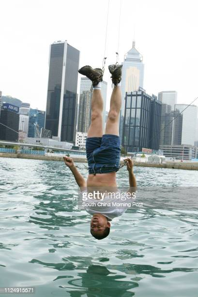 Special lunch time performance to view Beijing artist Li Wei who dangle himself on a crane on the waterfront Royal HK Yacht Club Kellett Island...