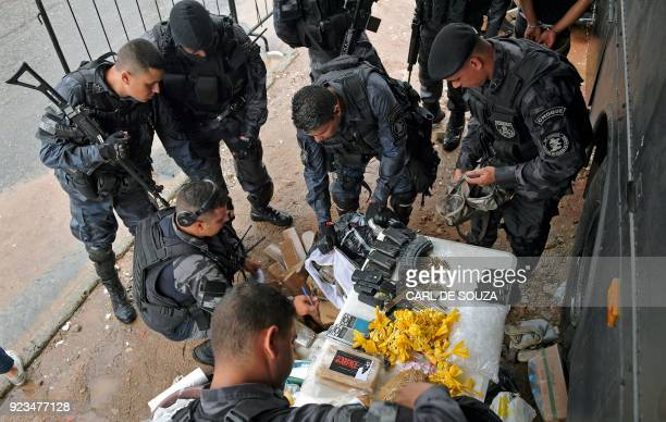 Special military police shock troops inspect seized drugs guns and ammunition close to the Vila Kennedy favela in Rio de Janeiro on February 23 2018...