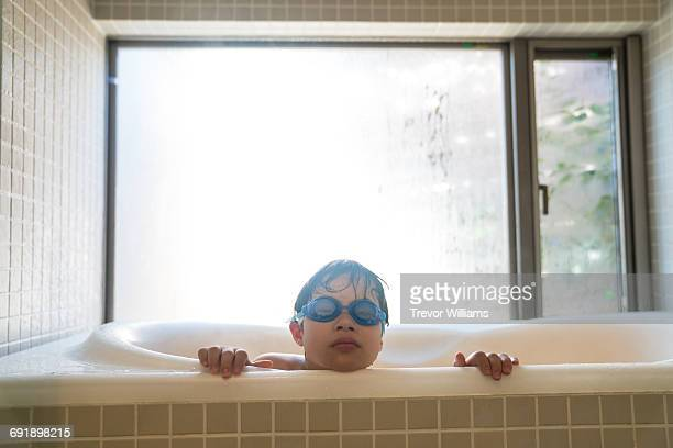Special needs boy peeking out of the bath tub