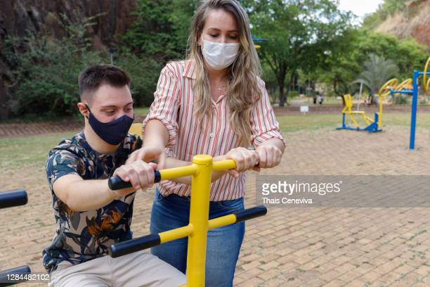 special needs boy with down syndrome  exercising outdoors - intellectually disabled stock pictures, royalty-free photos & images