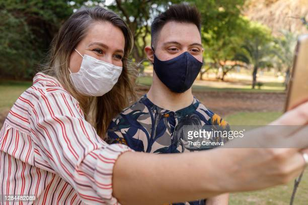 special needs boy with down syndrome taking a selfie with a friend - learning disability stock pictures, royalty-free photos & images