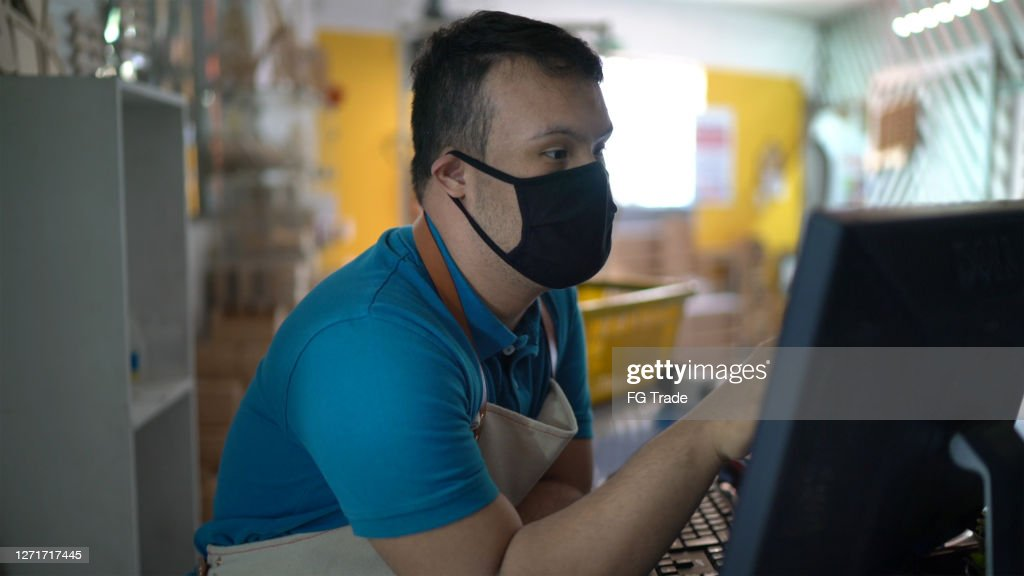 Special needs boy working touching monitor at store - wearing face mask : Stock Photo