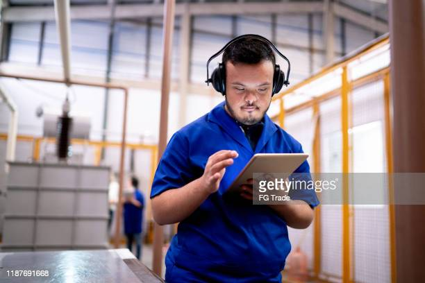 special needs employee using digital tablet in industry - persons with disabilities stock pictures, royalty-free photos & images