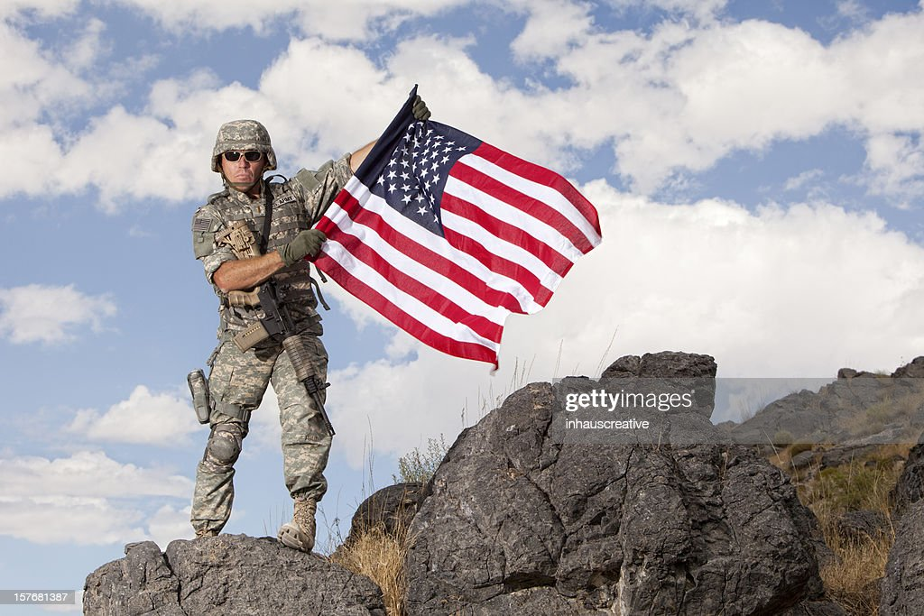 Special ops military soldier holding an american flag : Stock Photo