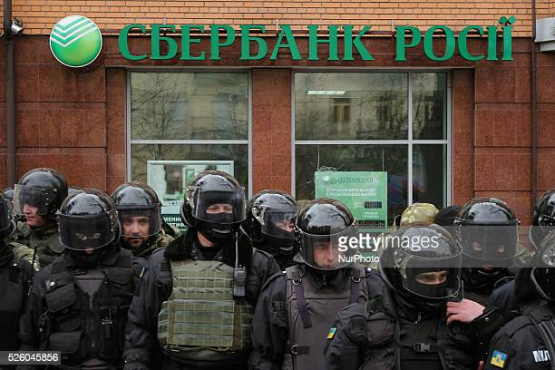 Special police forces and National Guards are seen patrolling the street next to the Sberbank of Russia office as radical nationalists protest...