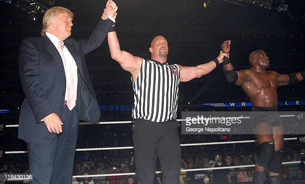 Special referee Steve Austin holds up the arms of Donald Trump and Bobby Lashley after their team won the 'Battle of the Billionaires' match at...