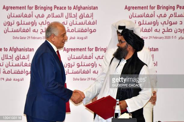 Special Representative for Afghanistan Reconciliation Zalmay Khalilzad and Taliban co-founder Mullah Abdul Ghani Baradar shake hands after signing a...