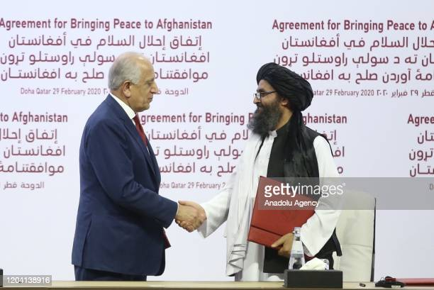 Special Representative for Afghanistan Reconciliation Zalmay Khalilzad and Taliban cofounder Mullah Abdul Ghani Baradar shake hands after signing the...
