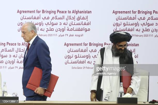 Special Representative for Afghanistan Reconciliation Zalmay Khalilzad and Taliban co-founder Mullah Abdul Ghani Baradar are seen after signing the...